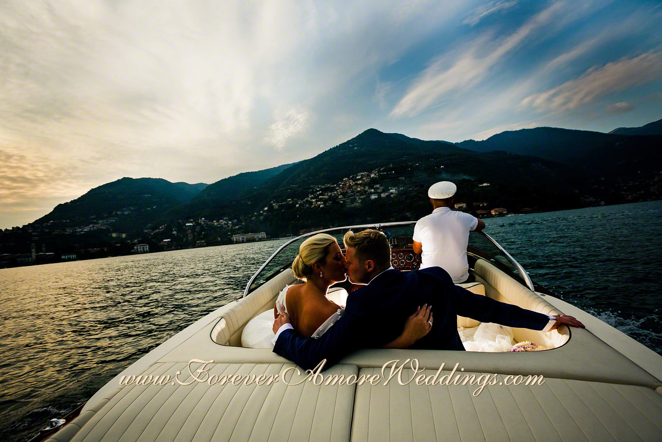 bridal couple kissing on the boat at sunset